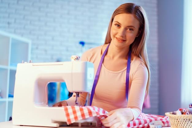 Giovane cucitrice allegra che si siede al tavolo di lavoro nel suo ufficio