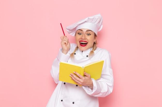 Giovane cuoco femminile di vista frontale in vestito bianco del cuoco che tiene il quaderno e matita gialli sul cuoco rosa dello spazio