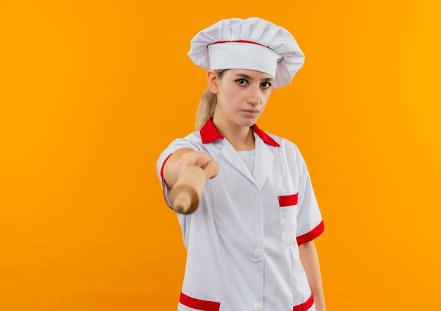 Giovane cuoco grazioso in uniforme del cuoco unico che allunga il mattarello