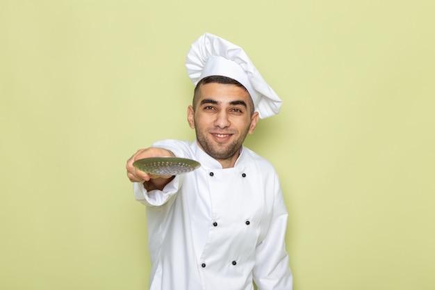 Giovane cuoco maschio di vista frontale in vestito bianco del cuoco che indica cucchiaio d'argento sul verde
