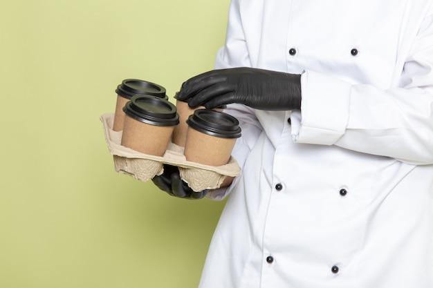 Giovane cuoco maschio di vista frontale in vestito bianco del cuoco che porta i guanti scuri e che tengono le tazze di caffè sul verde