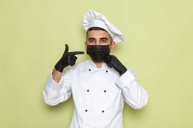 Giovane cuoco maschio di vista frontale in vestito bianco del cuoco che porta i guanti scuri e la mascherina sterile sul verde
