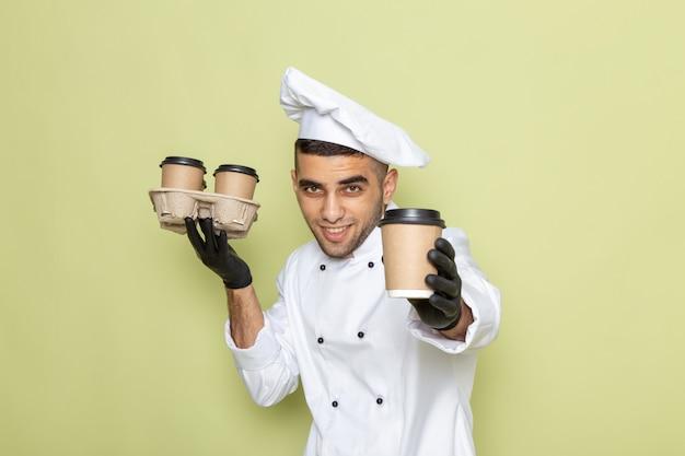 Giovane cuoco maschio di vista frontale in vestito bianco del cuoco che sorride e che tiene le tazze di caffè sul verde