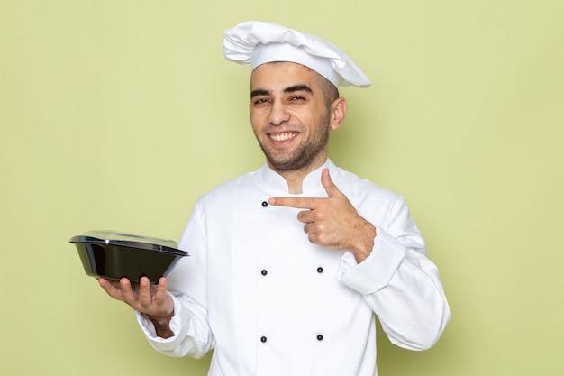 Giovane cuoco maschio di vista frontale in vestito bianco del cuoco che tiene la ciotola nera dell'alimento e che sorride sul verde