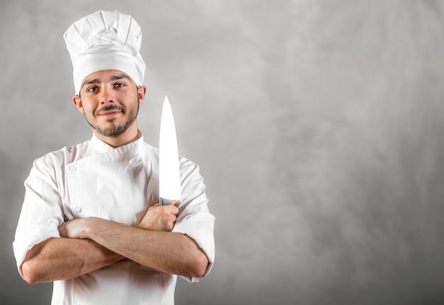 Giovane cuoco unico con il coltello che posa con il copyspace grigio della parete