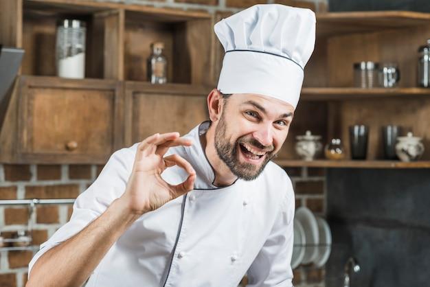 Giovane cuoco unico maschio felice che fa segno giusto