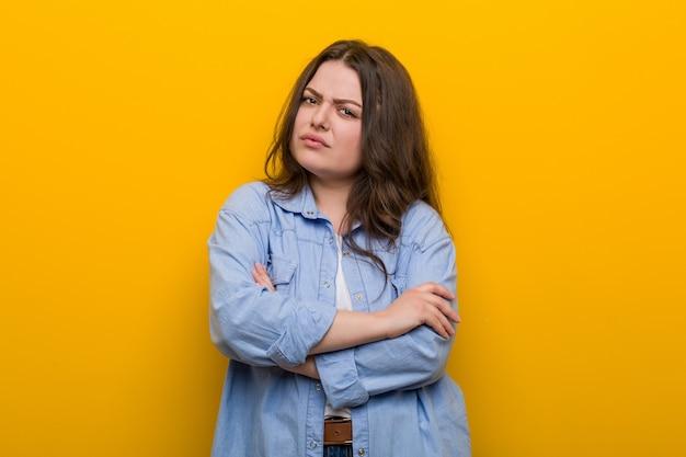 Giovane curvy plus size donna infelice guardando a porte chiuse con espressione sarcastica.
