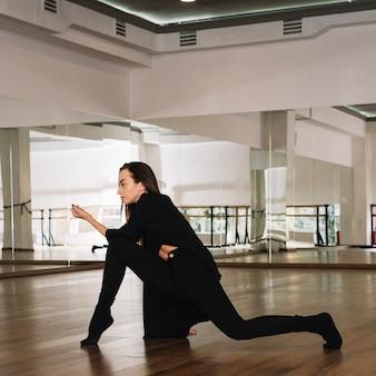 Giovane danzatore femminile che pratica nello studio di ballo