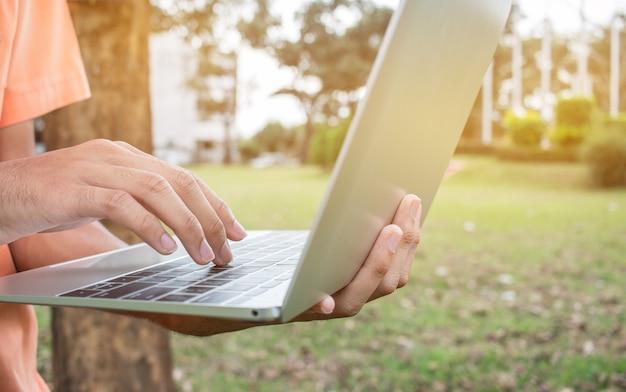 Giovane degli studenti che utilizza computer portatile nel parco su erba verde a scuola