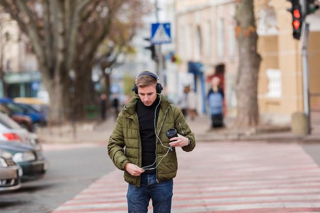 Giovane del colpo medio che ascolta la musica sulle cuffie fuori