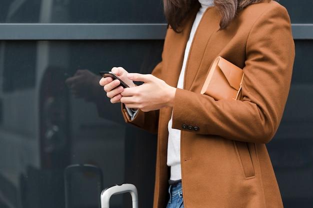 Giovane del primo piano che controlla il suo telefono