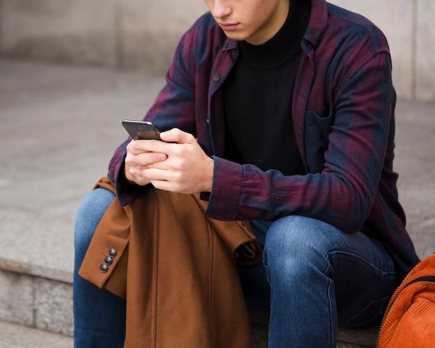 Giovane del primo piano che passa in rassegna il suo telefono