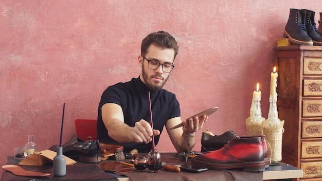 Giovane designer di scarpe che utilizza una spazzola mentre lavora nel negozio di scarpe con interni moderni