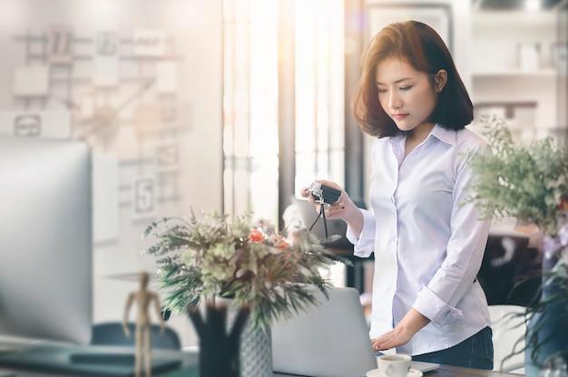 Giovane designer femminile nella macchina fotografica della tenuta di abbigliamento casual e nel funzionamento del computer portatile