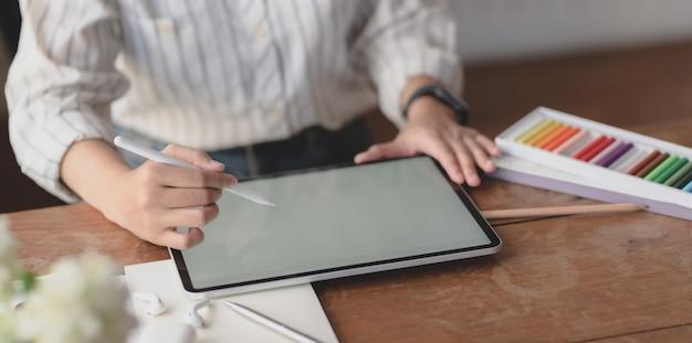 Giovane designer professionista femminile che lavora su tablet schermo vuoto nella sua area di lavoro