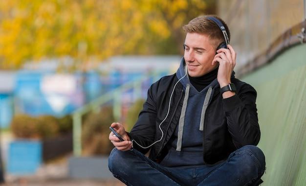 Giovane di smiley che ascolta la musica sulle cuffie su un banco