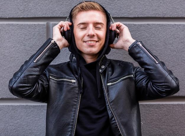 Giovane di smiley che ascolta la musica sulle cuffie
