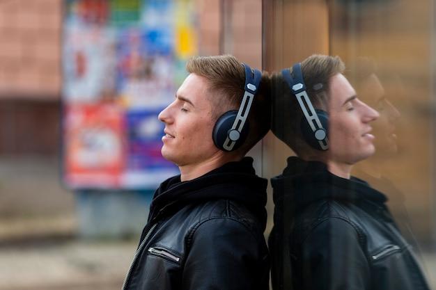 Giovane di vista laterale che ascolta la musica sulle cuffie