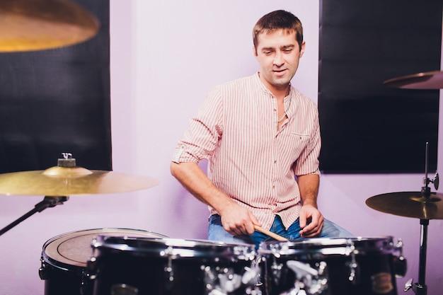 Giovane dietro installazione a tamburo in uno studio di registrazione professionale.