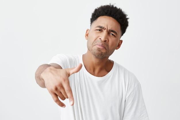 Giovane divertente bello maschio dalla pelle nera con l'acconciatura afro in maglietta bianca casual che punta a porte chiuse con la mano, facendo una faccia buffa, in posa per la foto con gli amici sulla festa.
