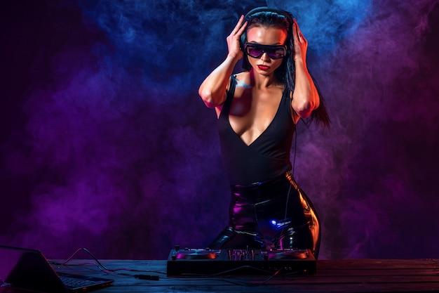 Giovane dj sexy con occhiali da sole che suona musica