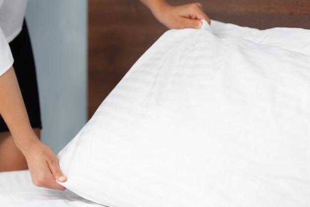 Giovane domestica che fa letto nella camera di albergo