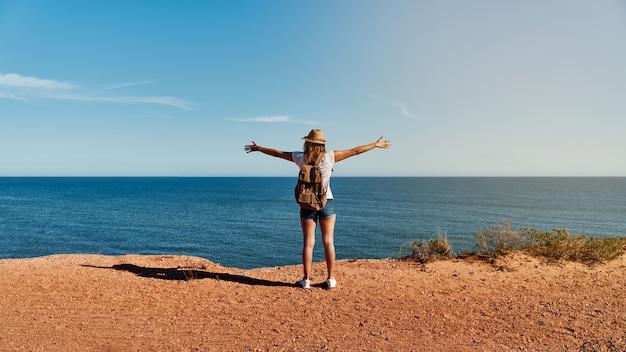 Giovane donna a braccia aperte, con cappello e zaino di fronte al mare in estate
