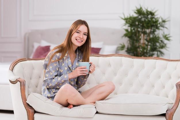 Giovane donna a casa che beve tè