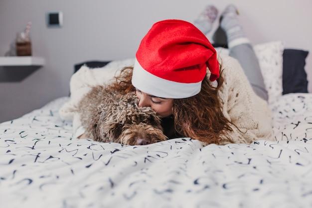 Giovane donna a casa che indossa un cappello santa baciando il suo cane sul letto. ambientazione interna. concetto di natale