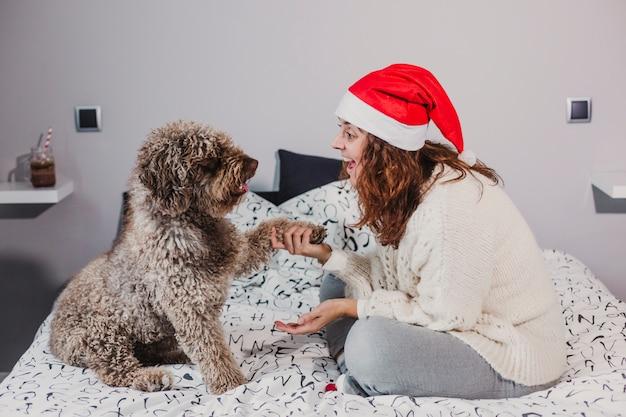 Giovane donna a casa che indossa un cappello santa giocando con il suo cane sul letto. ambientazione interna. concetto di natale
