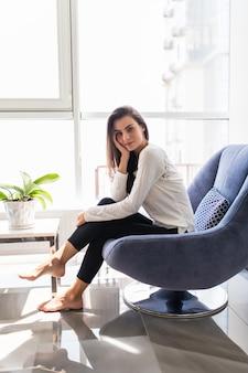 Giovane donna a casa che si siede sulla sedia moderna davanti alla finestra che si rilassa nel suo salone