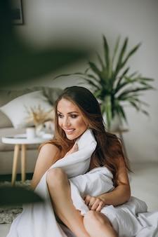 Giovane donna a casa coperta in coperta