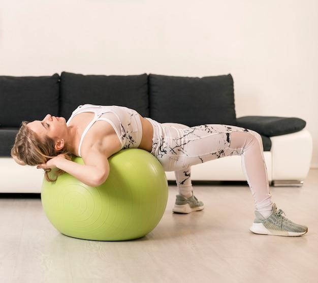 Giovane donna a casa lavorando su palla fitness
