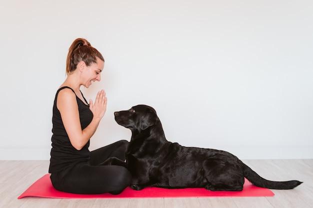 Giovane donna a casa rilassata usando la casa mobile. seduto su una stuoia di yoga con il suo cane labrador nero inoltre. tecnologia e