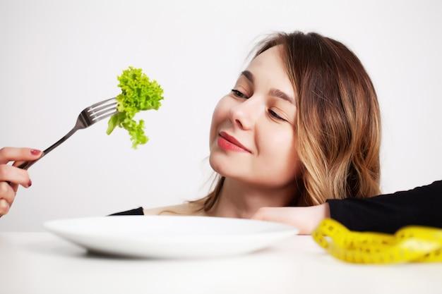 Giovane donna a dieta, mangia solo insalata e cerca di perdere peso