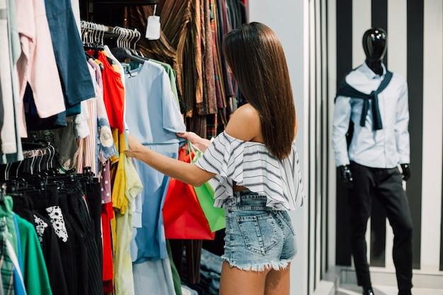 Giovane donna a fare shopping nel negozio