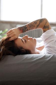 Giovane donna a letto al mattino