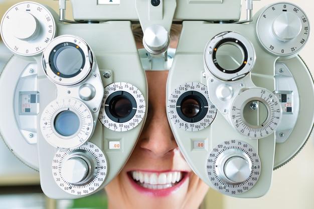 Giovane donna a phoropter per la prova dell'occhio