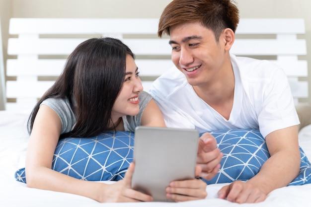 Giovane donna abbastanza asiatica ed uomo bello che si trovano sul letto nella camera da letto a casa