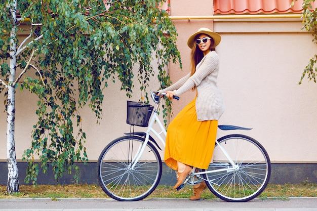 Giovane donna abbastanza bella in sella alla sua bici hipster retrò bianca, indossando occhiali da sole eleganti abiti vintage e cappello di paglia, moda autunno autunno ritratto di elegante signora divertendosi all'aperto.