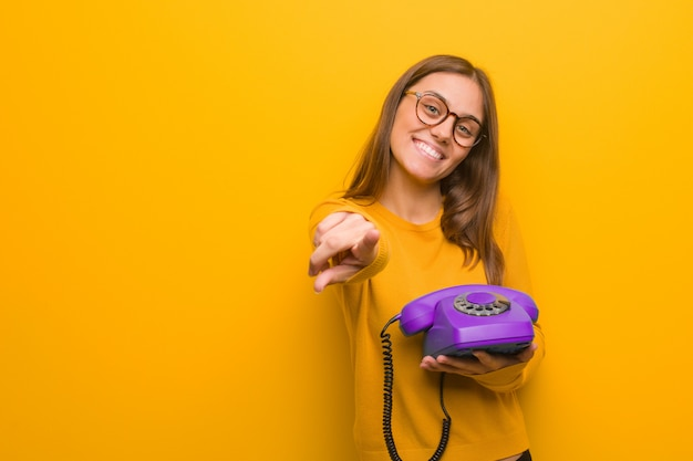Giovane donna abbastanza caucasica allegra e sorridente che punta alla parte anteriore. ha in mano un telefono vintage.