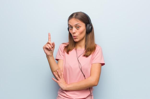 Giovane donna abbastanza caucasica che ha una grande idea, creatività. sta ascoltando musica con le cuffie.