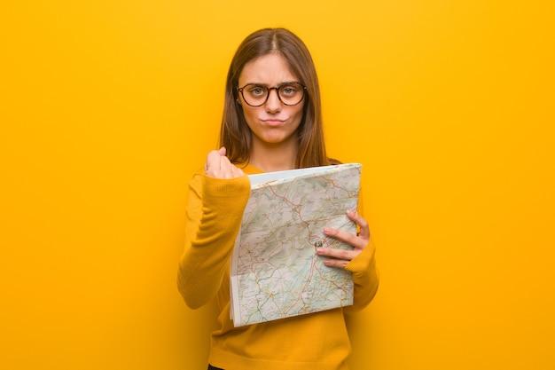 Giovane donna abbastanza caucasica che mostra il pugno di fronte, espressione arrabbiata. ha in mano una mappa.