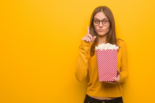 Giovane donna abbastanza caucasica che mostra numero uno. sta mangiando popcorn.