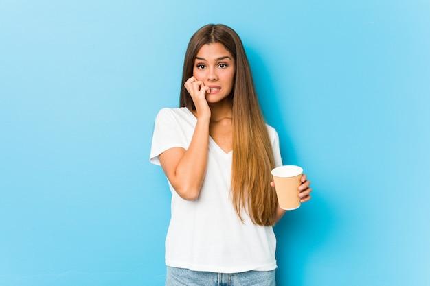 Giovane donna abbastanza caucasica che tiene le unghie mordaci di un caffè asportabile, nervose e molto ansiose.