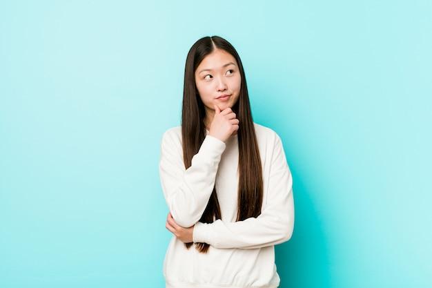 Giovane donna abbastanza cinese che guarda lateralmente con espressione dubbiosa e scettica.
