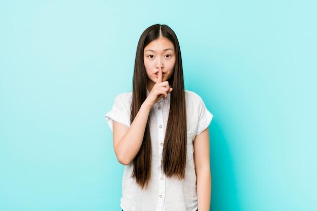 Giovane donna abbastanza cinese che mantiene un segreto
