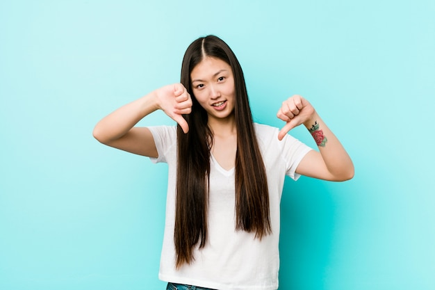 Giovane donna abbastanza cinese che mostra il pollice verso il basso e che esprime antipatia.
