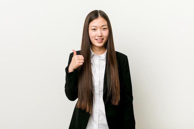 Giovane donna abbastanza cinese di affari che sorride e che alza pollice in su