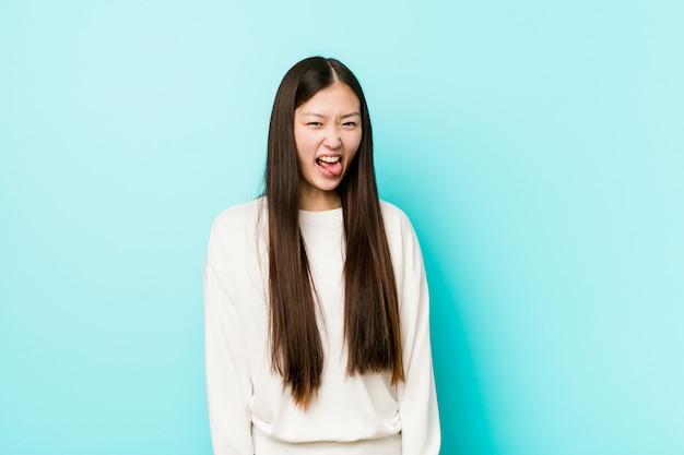 Giovane donna abbastanza cinese divertente e amichevole che attacca fuori lingua.
